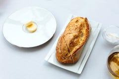 现代法国开胃菜:新鲜的被烘烤的面包用黄油服务与橄榄油 库存照片