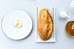 现代法国开胃菜:新鲜的被烘烤的面包用黄油服务与橄榄油 免版税库存照片
