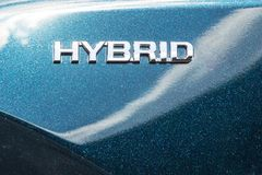现代混合动力车辆特写镜头侧视图  在金属发光的汽车防御者的杂种标志 futur绿色eco能量  免版税库存照片