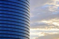 现代玻璃摩天大楼门面的侧视图在晚日出天空背景的 库存图片