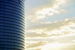 现代玻璃摩天大楼门面的侧视图在晚日出天空背景的 库存照片
