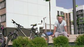 现代生活在一个大城市-基于一条长凳的运动的年轻人在城市在自行车乘驾以后 影视素材