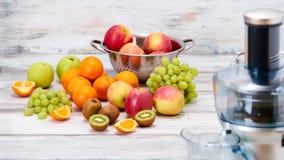 现代电榨汁器和各种各样的果子在厨台,健康生活方式戒毒所概念 免版税库存照片