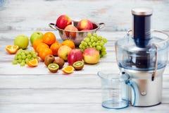 现代电榨汁器和各种各样的果子在厨台,健康生活方式,戒毒所概念 免版税库存图片