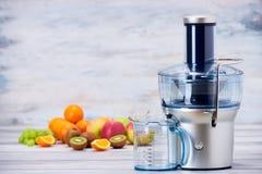 现代电榨汁器和各种各样的果子在厨台,健康生活方式,戒毒所概念 库存图片