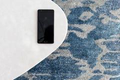 现代白色凳子由人为石头制成在有美好的休息的一张地毯,一张顶视图站立 手机在一把新的椅子说谎 免版税库存图片