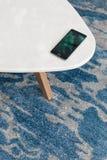 现代白色凳子由人为石头制成在有美好的休息的一张地毯,一张顶视图站立 手机在一把新的椅子说谎 免版税图库摄影
