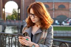 现代红头发人少妇在公园在秋天使用巧妙的电话 有卷曲姜发型的女孩,发短信,微笑,站立胜过 免版税库存照片