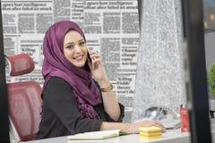 现代聪明的女性伊斯兰教的办公室工作者谈话在电话 库存图片