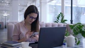 现代聪明的技术、在手机拍摄的愉快的成功的妇女在工作期间在手提电脑和作为 股票视频