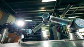 现代胳膊与在桌上的一个齿轮一起使用 影视素材