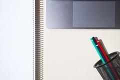 现代膝上型计算机和五颜六色的铅笔在持有人在轻的木选项 免版税库存图片