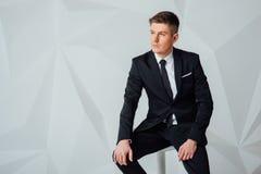 现代衣服的年轻商人坐椅子 库存照片