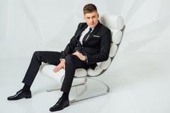 现代衣服的年轻商人坐椅子 免版税库存图片