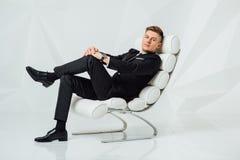 现代衣服的年轻商人坐椅子 库存图片