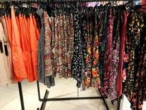 现代衣裳在挂衣架的一家商店 图库摄影