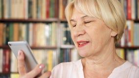 现代资深妇女在家谈话通过信使app在图书馆里 书橱书架在背景中 股票视频