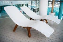 现代轻便折叠躺椅在豪华旅馆 放松的私有游泳池,与美好的内部 免版税库存图片