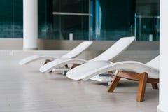 现代轻便折叠躺椅在豪华旅馆 放松的私有游泳池,与美好的内部 图库摄影