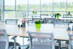 现代轻的空的露天场所办公室内部有大窗口、桌书桌、椅子和绿色植物的 Coworking工作场所conce 免版税库存图片