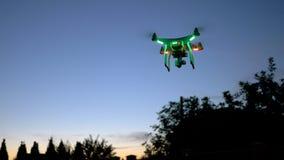 现代遥控空气寄生虫飞行高与在日落天空的行动照相机 都市风景剪影在背景中 现代technolo 免版税库存照片