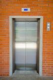 现代钢门电梯和橙色砖墙 库存照片