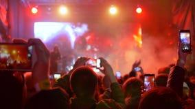 现代青年时期休闲,在手观众的手机拍摄摇滚乐音乐会录影在明亮地被点燃的阶段的 股票录像