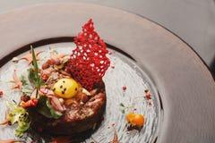 现代餐馆盘 小牛肉鞑靼与鹌鹑蛋特写镜头 免版税库存图片