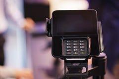 现代黑数字电话或终端有一个键盘和一个屏幕的在机架在办公室 免版税库存照片