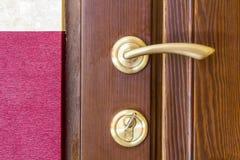 现代,当代缎金属把柄和一把钥匙在锁在w 免版税库存图片