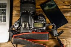现代DSLR照相机、智能手机和膝上型计算机在木桌上 名列前茅v 库存图片