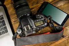 现代DSLR照相机、智能手机和膝上型计算机在木桌上 名列前茅v 免版税库存图片