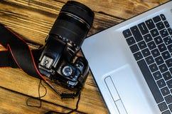 现代DSLR照相机和膝上型计算机在木桌上 顶视图 图库摄影