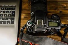 现代DSLR照相机和膝上型计算机在木桌上 顶视图 免版税图库摄影