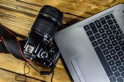现代DSLR照相机和膝上型计算机在木桌上 顶视图 库存图片