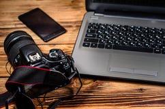 现代DSLR照相机和膝上型计算机在木桌上 免版税库存照片