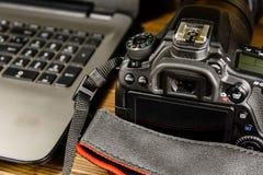 现代DSLR照相机和膝上型计算机在木桌上 库存照片