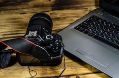 现代DSLR照相机和膝上型计算机在木桌上 免版税图库摄影