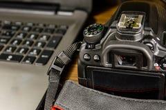 现代DSLR照相机和膝上型计算机在木桌上 图库摄影