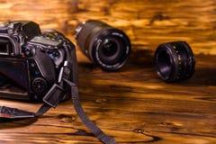 现代dslr照相机和透镜在木桌上 免版税库存图片