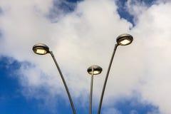 现代LED光弯曲的杆 蓝色照明设备天空街道村庄 图库摄影
