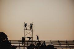 现出轮廓一个小组的图象工作在建筑的脚手架的工作者 免版税库存图片