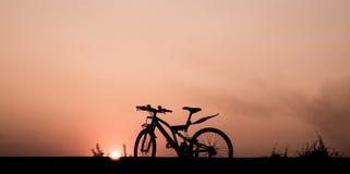 现出轮廓一辆自行车有在中间路的美好的暮色天空背景 免版税图库摄影