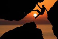 现出轮廓上升在与红色天空日落backgr的岩石之间的人 免版税库存照片