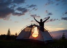 现出轮廓与她的手被上升的天空的旅游女性身分在山顶部靠近露营地在日落 查出的背面图白色 免版税库存照片