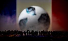 现出轮廓人群在一个大被弄脏的足球 创造性的概念 免版税库存照片