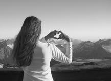 现出轮廓做心脏形状用她的手的女孩,招呼 库存图片