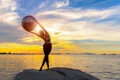 现出轮廓健康妇女行使重要在岩石思考和实践的瑜伽和健身房球在海滩日落的生活方式 免版税库存照片