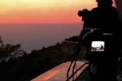 现出轮廓在三脚架的照相机有在暮色天空背景的美好的日落的 免版税图库摄影
