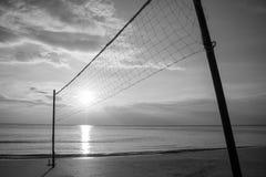 现出轮廓在沙子海滩的排球网与在暮色时间的美好的日落 免版税库存照片